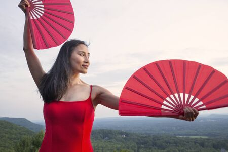Female dancer in red dress, raising at sunset on the mountain a red fan in each hand, at Penwood State Park in Bloomfield, Connecticut. Foto de archivo - 133024120