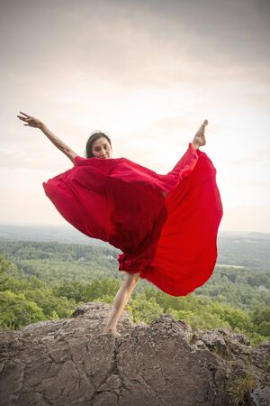Female dancer in flowing red dress, dancing on the rocky summit of the mountain at Penwood State Park in Bloomfield, Connecticut. Foto de archivo - 131784748