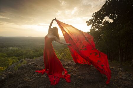 Female dancer in red dress, waving into the wind at sunset on the mountain a red fabric with Chinese calligraphy on it, at Penwood State Park in Bloomfield, Connecticut. Foto de archivo - 133024125