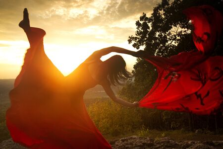 Female dancer in red dress, waving into the wind at sunset on the mountain a red fabric with Chinese calligraphy on it, at Penwood State Park in Bloomfield, Connecticut. Stock fotó