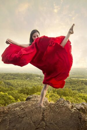 Female dancer in flowing red dress, dancing on the rocky summit of the mountain at Penwood State Park in Bloomfield, Connecticut. Foto de archivo - 133024241