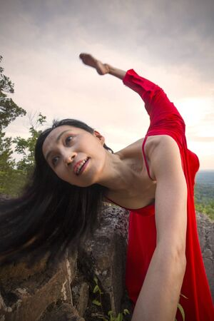 Closeup of female dancer in long red dress, doing a lunge and back kick on the rocky summit of the mountain at Penwood State Park in Bloomfield, Connecticut.
