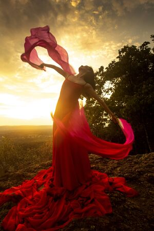 Female dancer in red dress, waving into the wind at sunset on the mountain a red fan with flowing fabric on it, at Penwood State Park in Bloomfield, Connecticut. Foto de archivo - 131648188