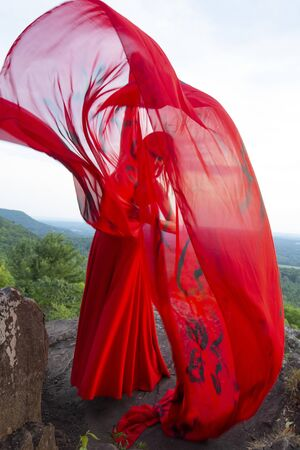 Female dancer in red dress, waving into the wind in late afternoon on the mountain, a red fabric with Chinese calligraphy on it, at Penwood State Park in Bloomfield, Connecticut. Foto de archivo - 131648254