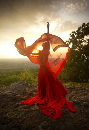 Female dancer in red dress, waving into the wind at sunset on the mountain a red fabric with Chinese calligraphy on it, at Penwood State Park in Bloomfield, Connecticut. Foto de archivo - 131649059