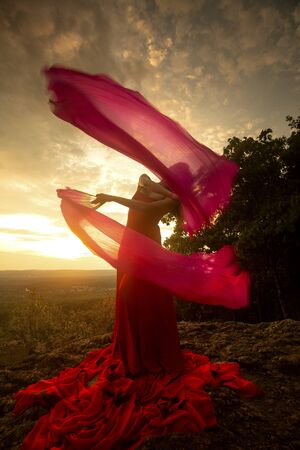 Female dancer in red dress, waving into the wind at sunset on the mountain a red fan with flowing fabric on it, at Penwood State Park in Bloomfield, Connecticut. Foto de archivo - 133024244