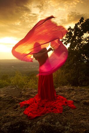 Female dancer in red dress, waving into the wind at sunset on the mountain a red fan with flowing fabric on it, at Penwood State Park in Bloomfield, Connecticut. Foto de archivo - 131648708