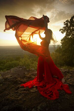 Female dancer in red dress, waving into the wind at sunset on the mountain a red fabric with Chinese calligraphy on it, at Penwood State Park in Bloomfield, Connecticut. Foto de archivo - 131648642