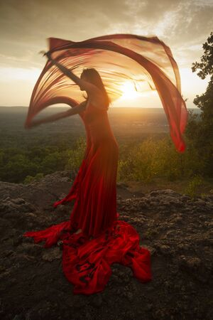 Female dancer in red dress, waving into the wind at sunset on the mountain a red fabric with Chinese calligraphy on it, at Penwood State Park in Bloomfield, Connecticut. Foto de archivo - 133024248
