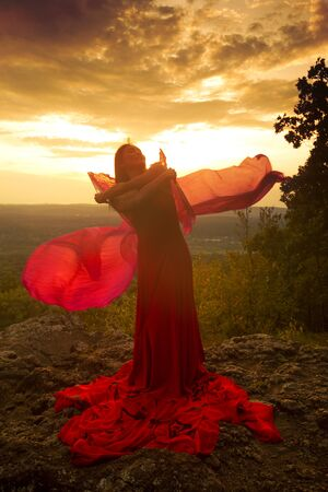 Female dancer in red dress, waving into the wind at sunset on the mountain a red fan with flowing fabric on it, at Penwood State Park in Bloomfield, Connecticut. Foto de archivo - 131648637