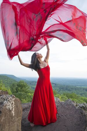 Female dancer in red dress, waving into the wind in late afternoon on the mountain, a red fabric with Chinese calligraphy on it, at Penwood State Park in Bloomfield, Connecticut.