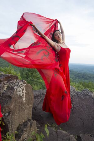 Female dancer in red dress, waving into the wind in late afternoon on the mountain, a red fabric with Chinese calligraphy on it, at Penwood State Park in Bloomfield, Connecticut. Foto de archivo - 133024249