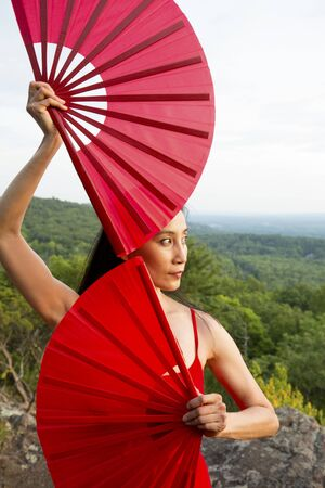 Female dancer in red dress, raising at sunset on the mountain a red fan in each hand, at Penwood State Park in Bloomfield, Connecticut.