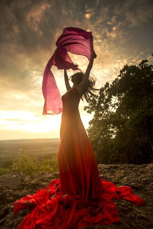 Female dancer in red dress, waving into the wind at sunset on the mountain a red fan with flowing fabric on it, at Penwood State Park in Bloomfield, Connecticut. Foto de archivo - 131648693