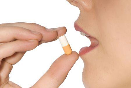tomar medicina: mujer tomando la p�ldora en un fondo blanco Foto de archivo