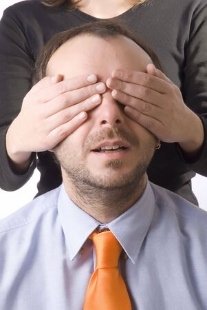 young woman covering the eyes of a business man photo