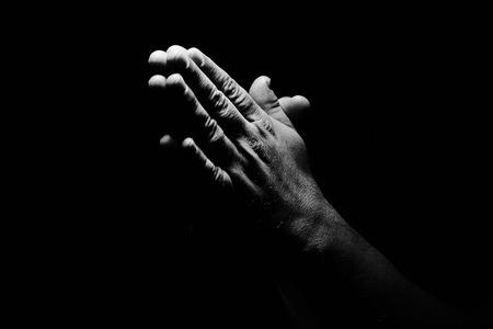 Biddende handen op zwarte achtergrond Stockfoto
