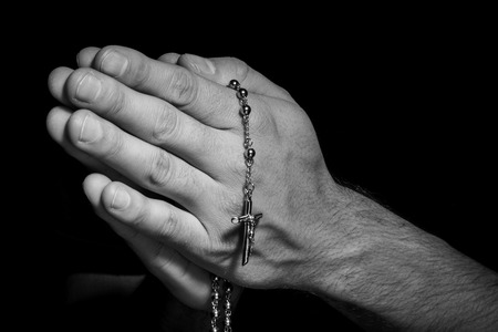 human hands: Praying Hands with rosay in black background black and withe