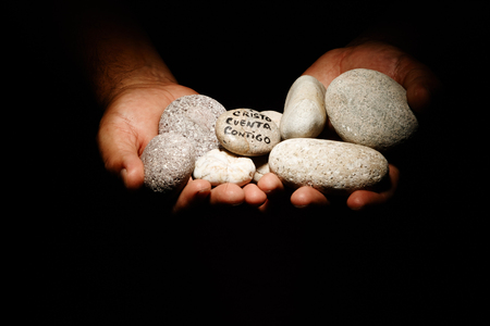 Praying hands with a rocks