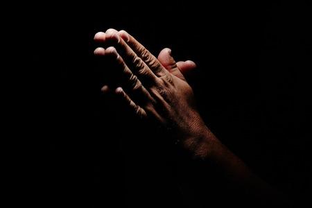 manos orando: Manos de rogación en el fondo negro