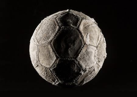 hape: Old and vinatage soccer ball dark on black background.