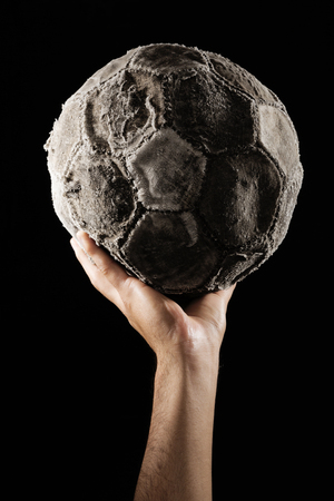 hape: man hand with Old and vinatage soccer ball on white background. Stock Photo