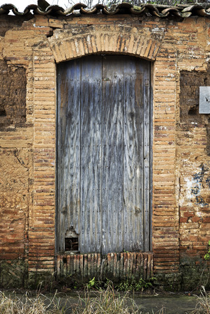 worn structure red: A vintage old wood door on the town of Jalisco, Mexico, America