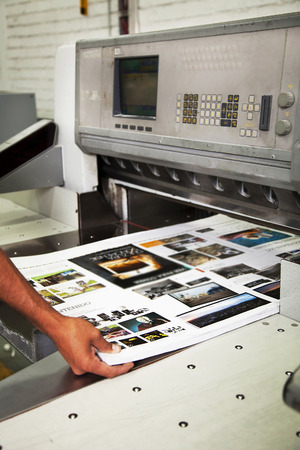 Hand man working in offset printing cut machine during production