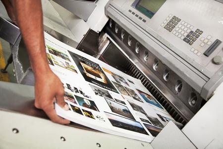 Uomo lavorare mano nella macchina di taglio stampa offset durante la produzione Archivio Fotografico - 62865485