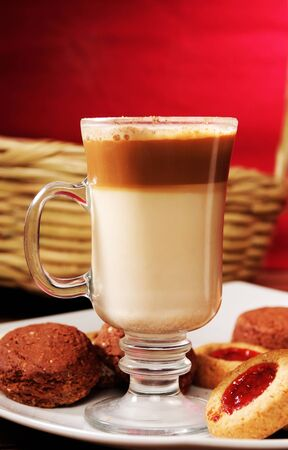 capuchino: Capuchino coffe and cookies in a plate with red background