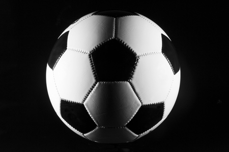 asiatic: Black and white soccer ball on black background. Stock Photo