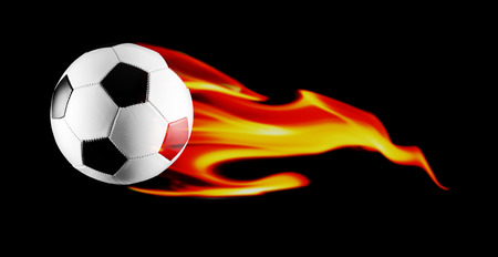 Black and white soccer ball with fire on black background. Stock Photo