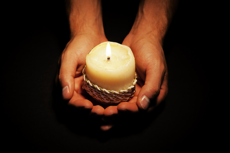 reverent: Praying Hands with candle in dark background
