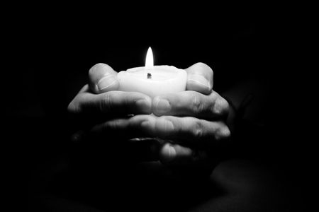 reverent: Praying Hands with candle in dark background black and white