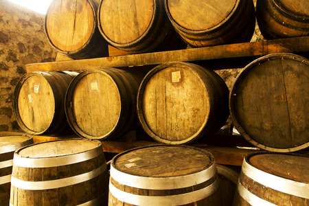 Wine barrels stacked in the old cellar of the winery. Stock Photo