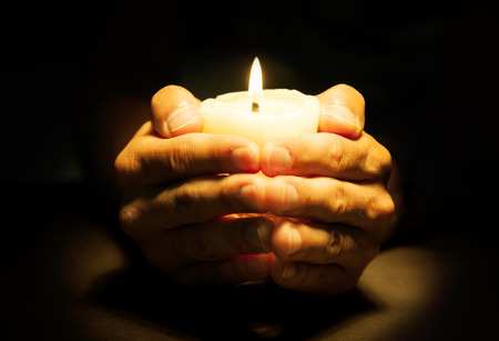 plead: Praying Hands with candle in black background Stock Photo