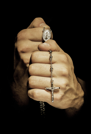 reverent: Hands man praying  with rosay in black background