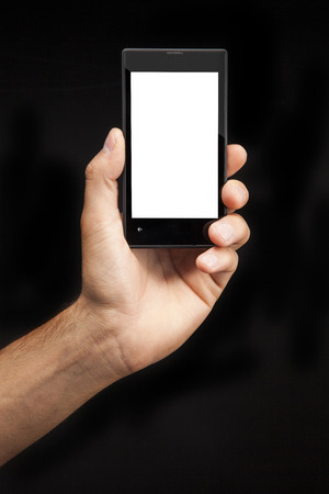 Hand holding  Smartphone with whitescreen on black background