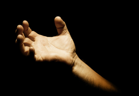 reverent: Man�s hand with pain signal in dark background Stock Photo