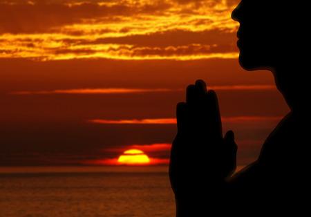 reverent: Man praying Outdoors. Nature. Sunset. Stock Photo