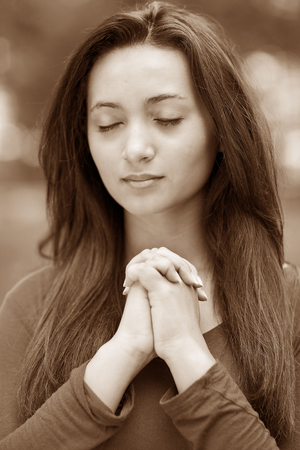 Woman hands praying with a blible in his legs Outdoors, sepia black and white Stock Photo