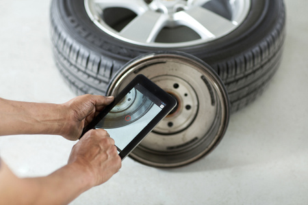 rin: Mechanic man hands working taken a photo to a tire with a tablet Stock Photo