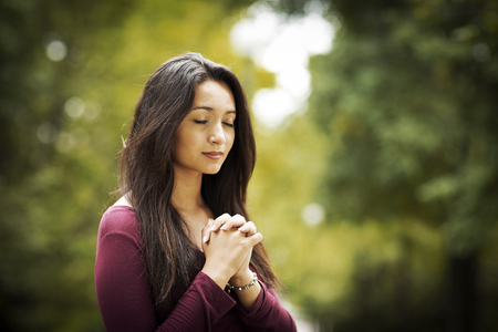reverent: Woman hands praying in the forest. Outdoors. Nature.