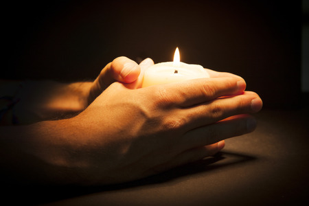 reverent: Praying Hands with candle in black background Stock Photo