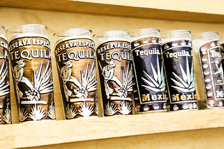 Several tequila souvenir glass in wood cabinet