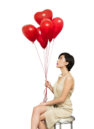 Fashion girl model posing with red heart bright balloons on white background.  Stock Photo