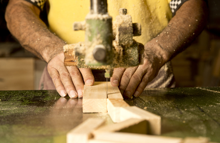 incus: Mans hand detail cutting wood at the industry of the manufacture.