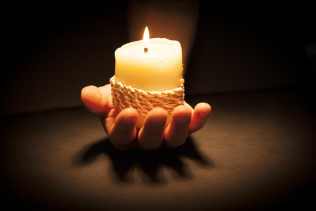 Praying Hands with candle in black background Stock Photo