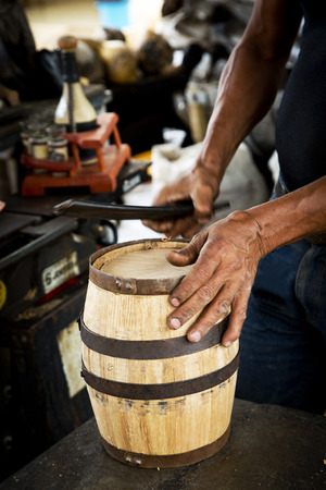 incus: Mans hand detail working at the industry of the decorative wine and tequila barrels.