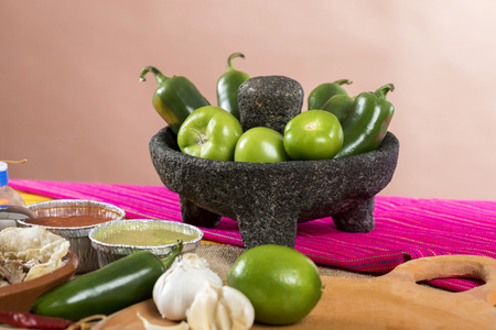 Typical Mexican food dishes with sauces on colorful table. Stone molcajete with chilies and green tomatoes Stock Photo